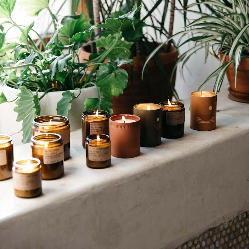 Window sill with a bunch of P.F. Candle Co.'s candles, like its amber jar and terra cotta candles