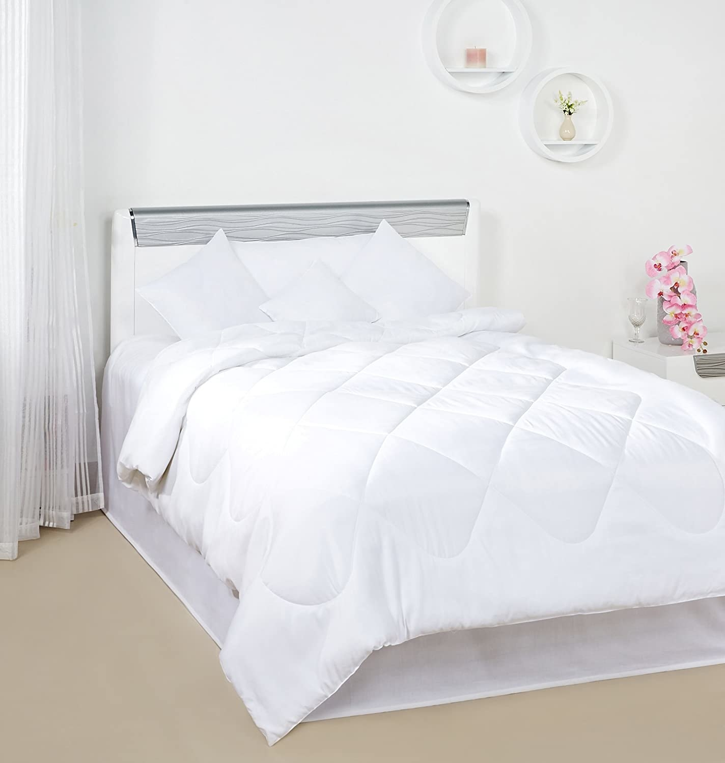 A white comforter spread out over a single bed