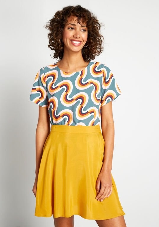a model wearing the slate blue t-shirt blouse with rainbows arranged in an opposite facing style across it tucked into a skirt