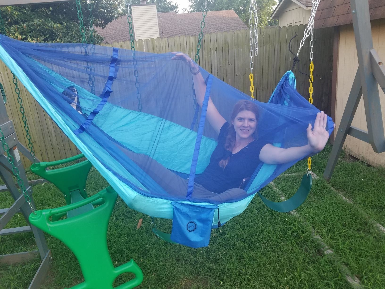 Reviewer spread out in the hammock with arms outstretched to show netting