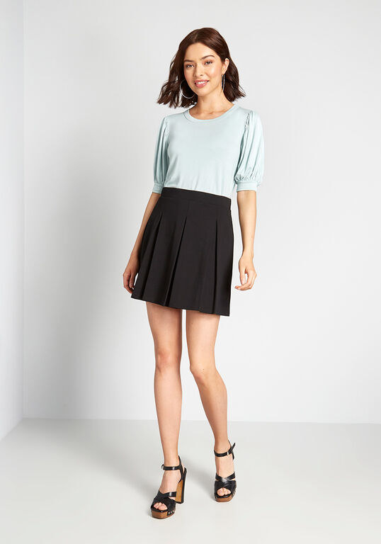 a model wearing the pleated mini skirt in black
