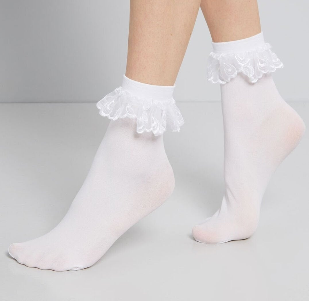white, dainty socks with frilly eyelet fabric hanging around the top ankle area