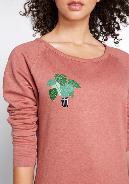 the coral colored sweatshirt with a graphic of a leafy plant in a black and white pot in the top right corner