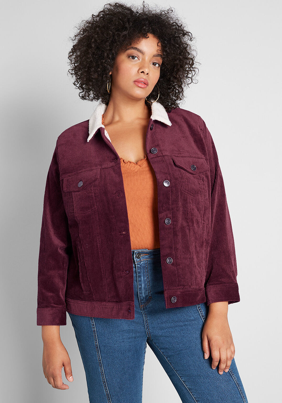 a model wearing the burgundy jacket with a white sherpa collar