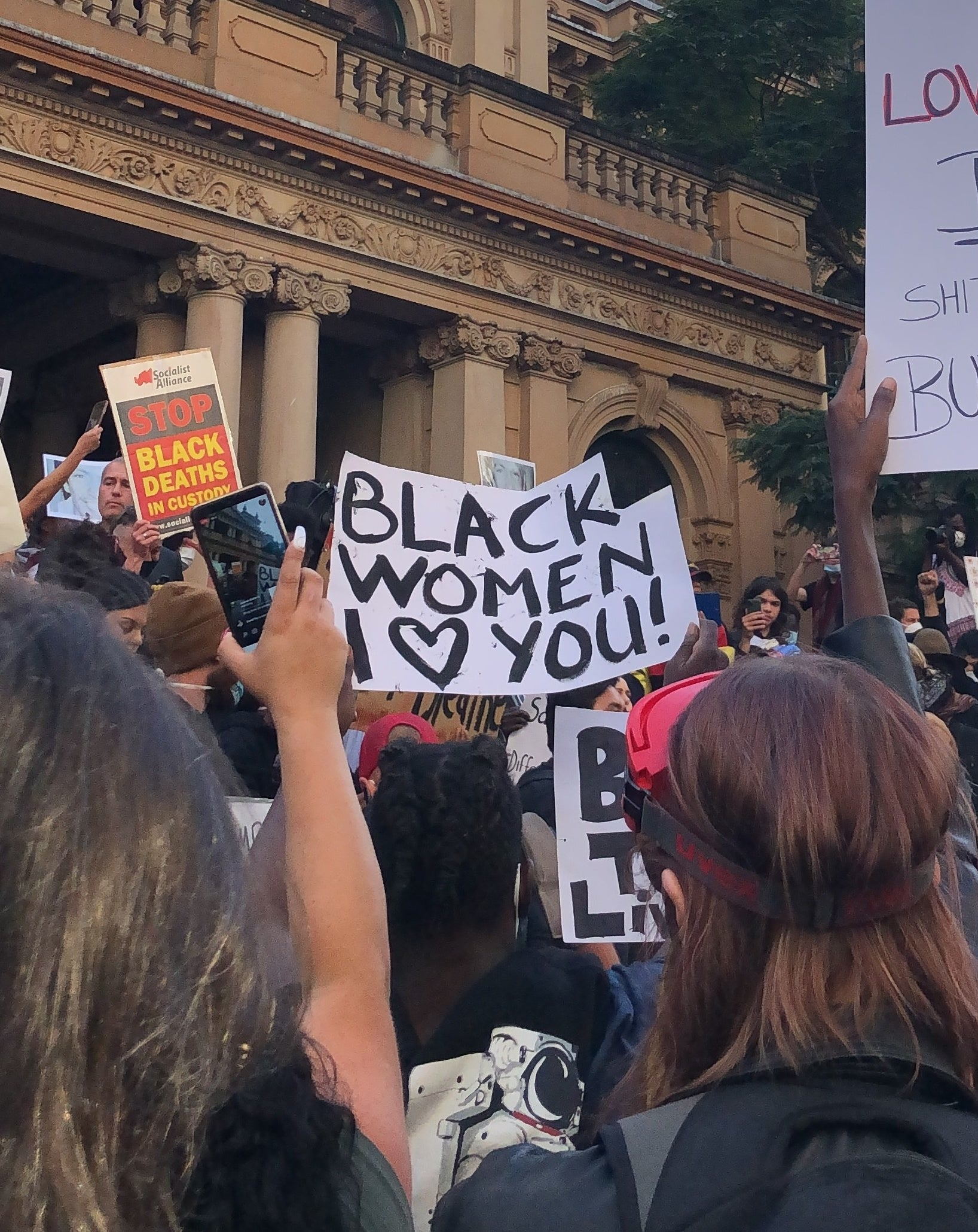 "A protest sign reads ""Black women, I love you""."