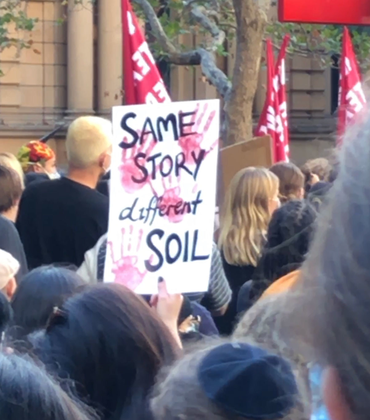 "A protest sign reads ""Same story, different soil""."