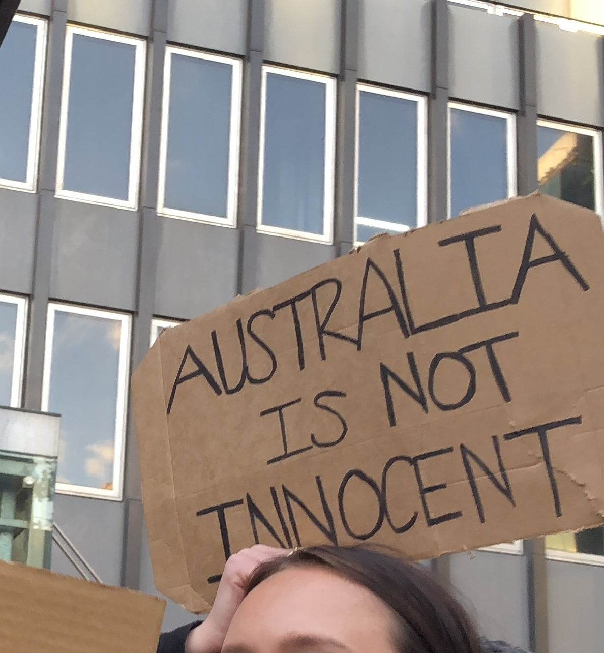 "A protest sign reads ""Australian is not innocent""."