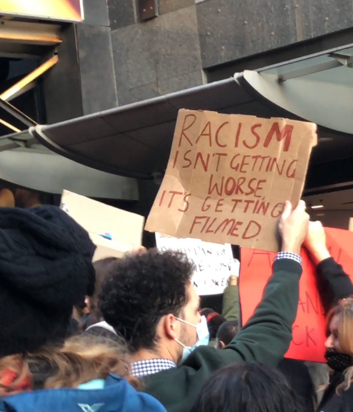 "A protest sign reads ""Racism isn't getting worse, it's getting filmed""."