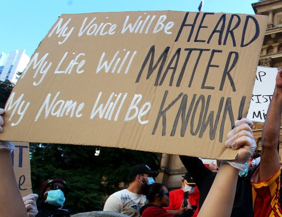 "A protest sign reads ""My voice will be heard, my life will matter, my name will be known""."