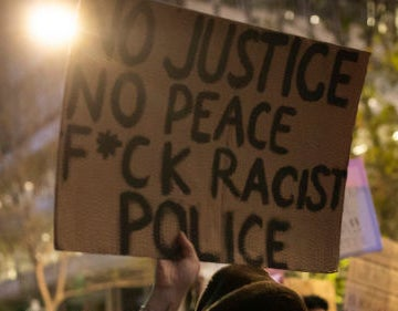 "A protest sign reads ""No justice, no peace, fuck racist police""."