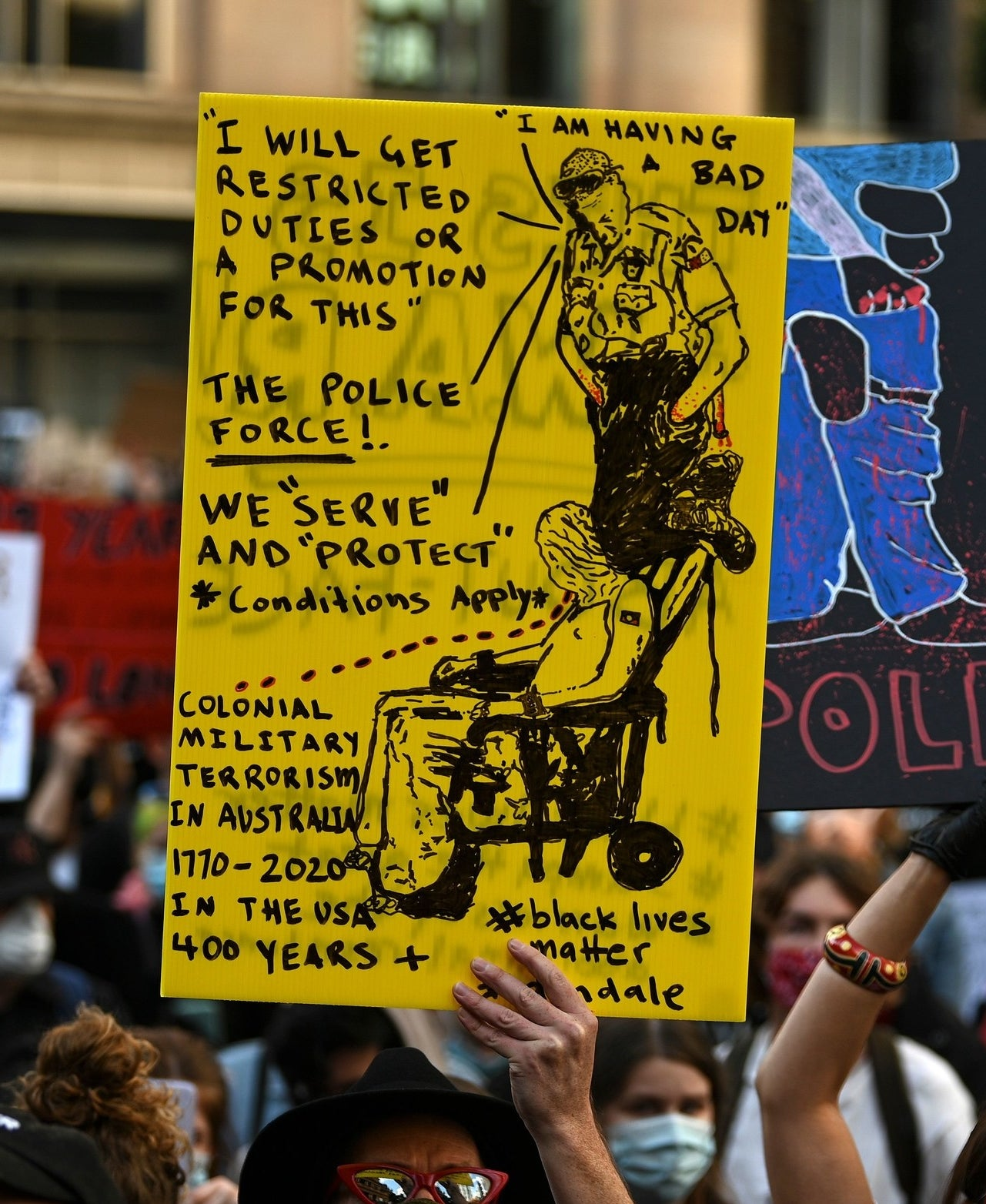 A protest sign depicting a police officer leaning on the neck of an innocent person.