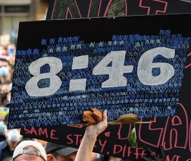 "A protest sign reads ""8:46""."