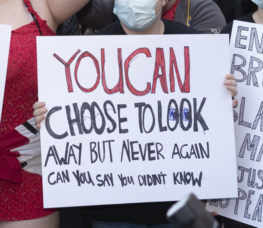 "A protest sign reads ""You can choose to look away, but never again can you say you didn't know""."