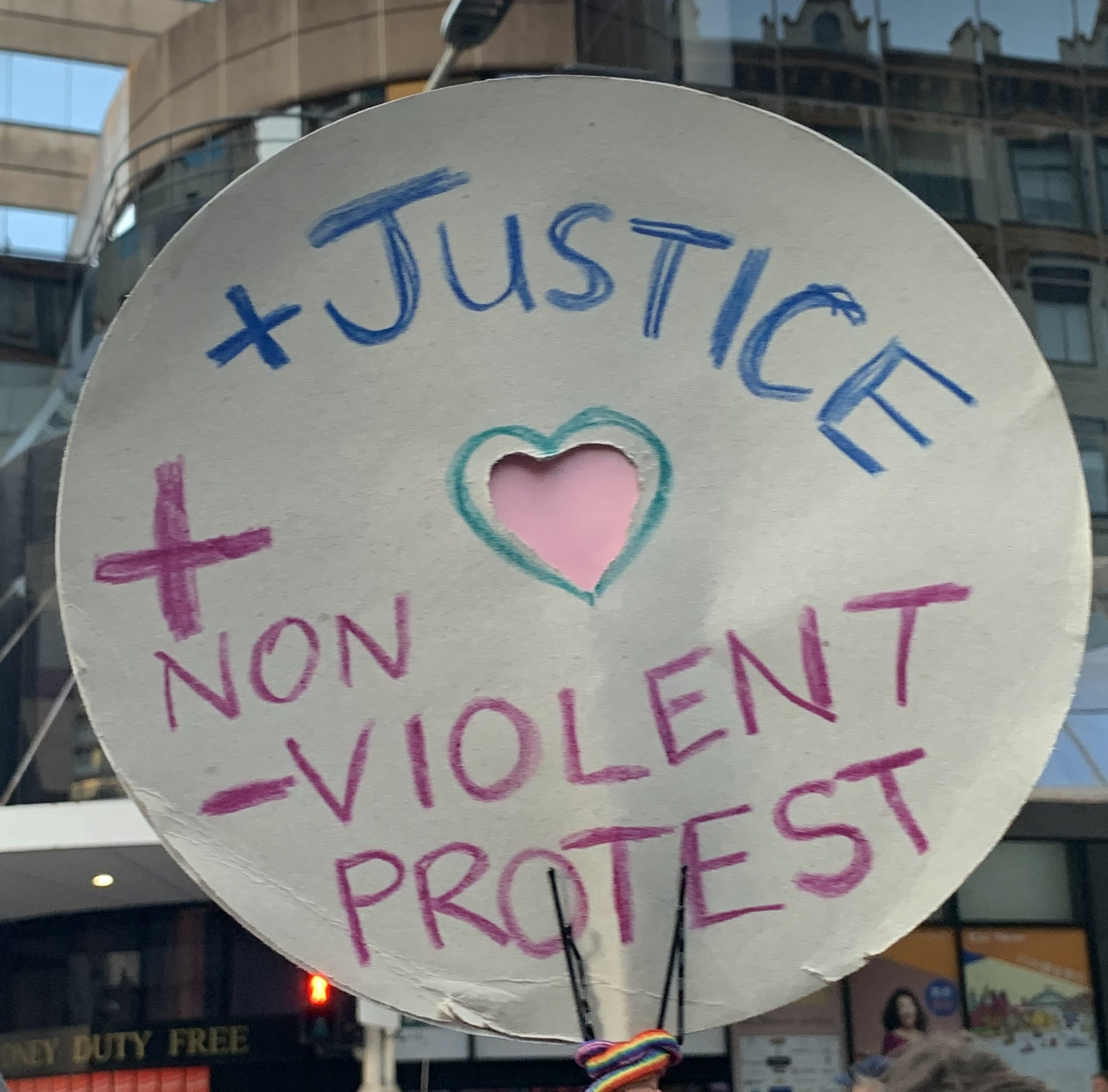 "A protest sign reads ""Justice + non-violent protest""."