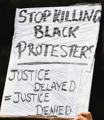"A protest sign reads ""Justice delayed = justice denied""."