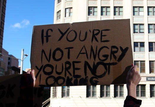 "A protest sign reads ""If you're not angry, you're not looking""."