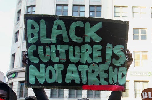 "A protest sign reads ""Black culture is not a trend""."