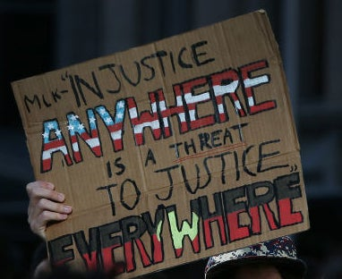 "A protest sign reads ""Injustice anywhere is a threat to justice everywhere""."