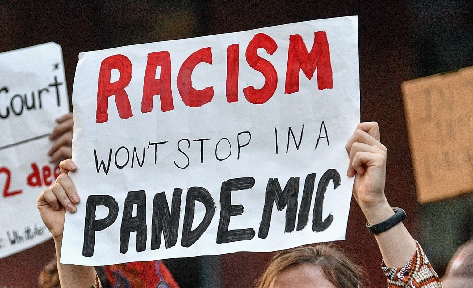 "A protest sign reads ""Racism won't stop in a pandemic""."