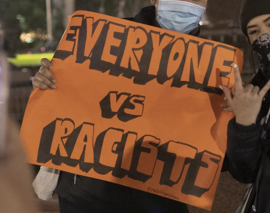 "A protest sign reads ""Everyone vs racists""."