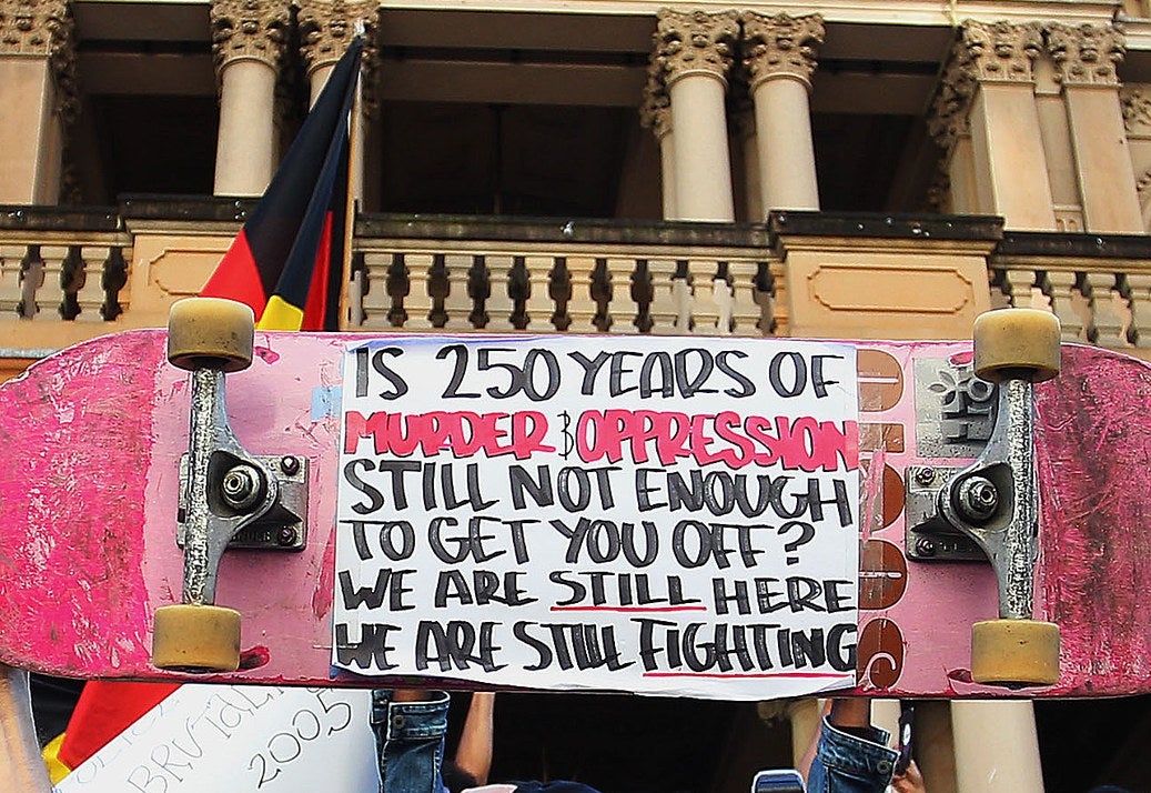 "A protest sign reads ""Is 250 years of murder and oppression still not enough to get you off? We are still here fighting""."