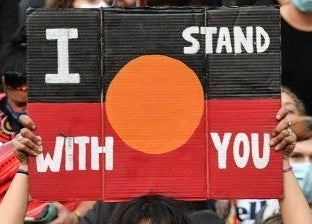 "A protest sign reads ""I stand with you""."