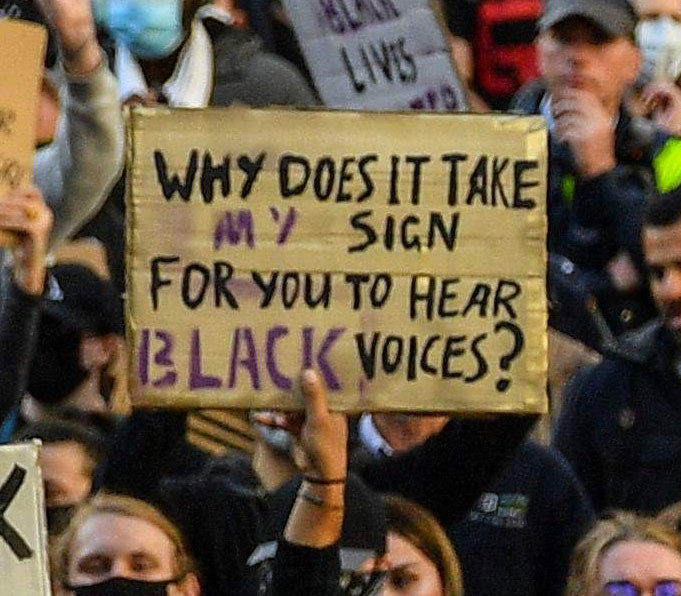 "A protest sign reads ""Why does it take my sign for you to hear black voices?"""