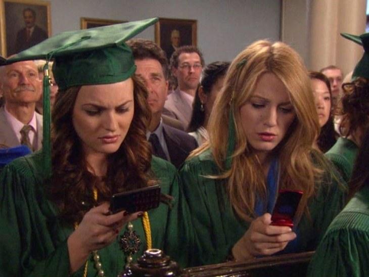 Serena and Blair looking at their phones at graduation