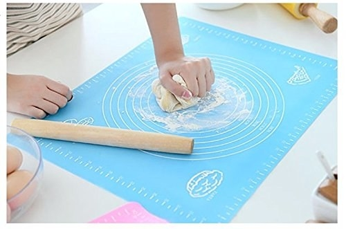 Dough being kneaded by hand on the rolling mat