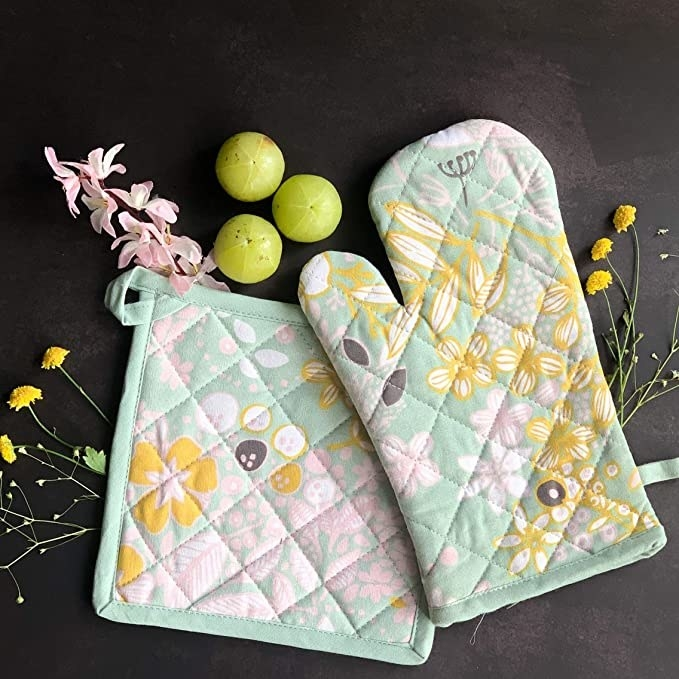 Oven mitten and pot holder on a table surrounded by flowers and gooseberries