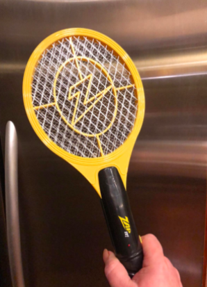 reviewer's hand holding up the zapper that looks like a small tennis racket