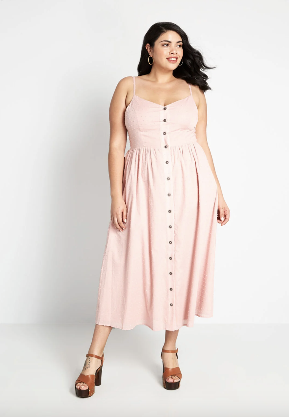 A model in a maxi dress with straps that buttons all the way up