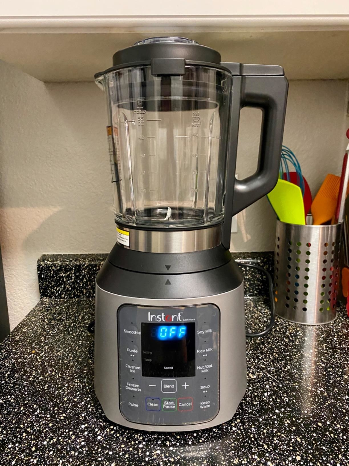 A reviewer's photo of a gray-metallic blender with a digital screen
