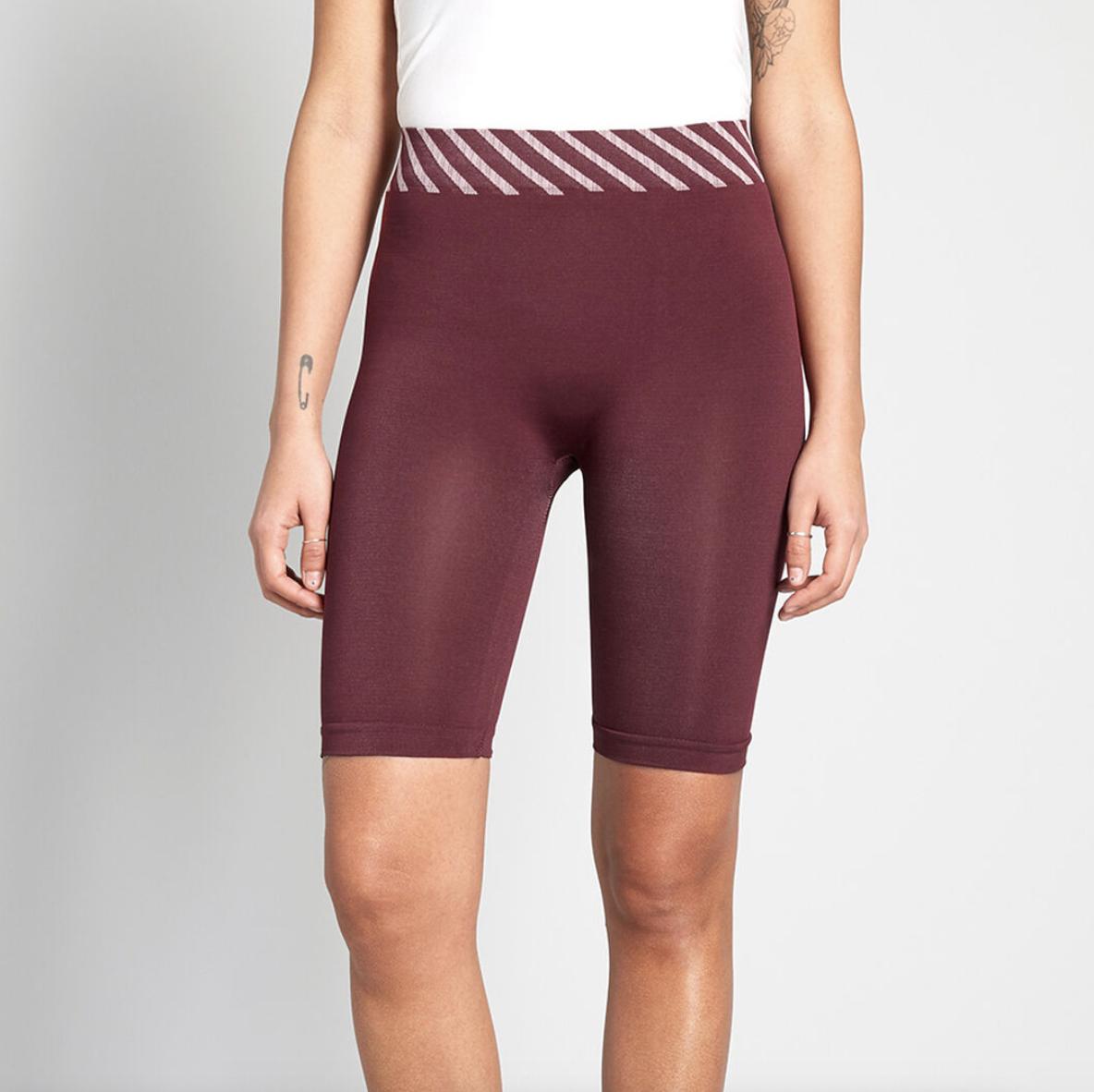 a model wearing the maroon stretchy bike shorts