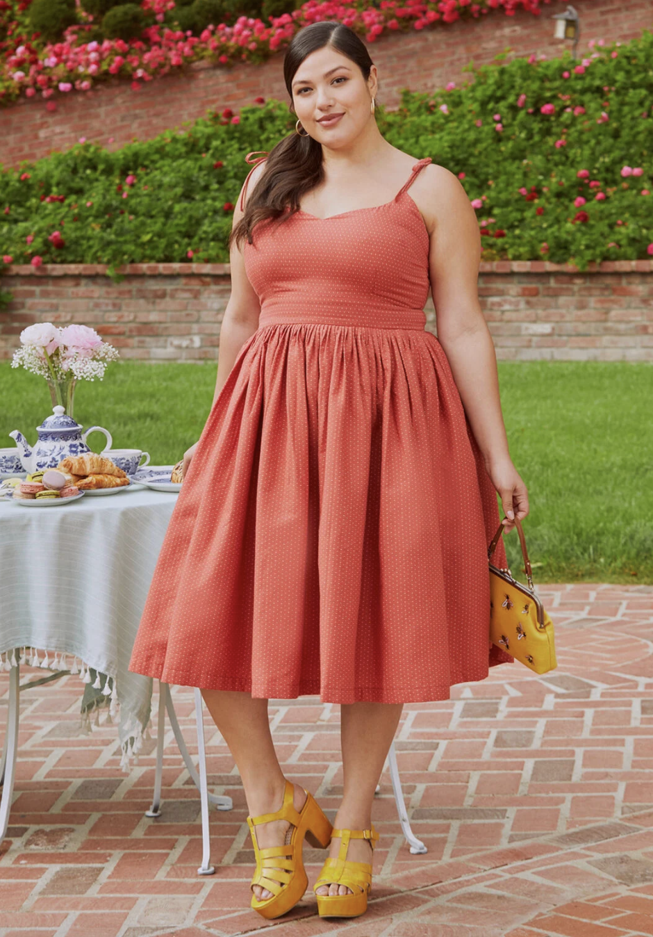 A model in the orange dress, which falls just below the knee