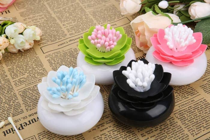 four pots with lily flowers on top and an opening for cotton swabs