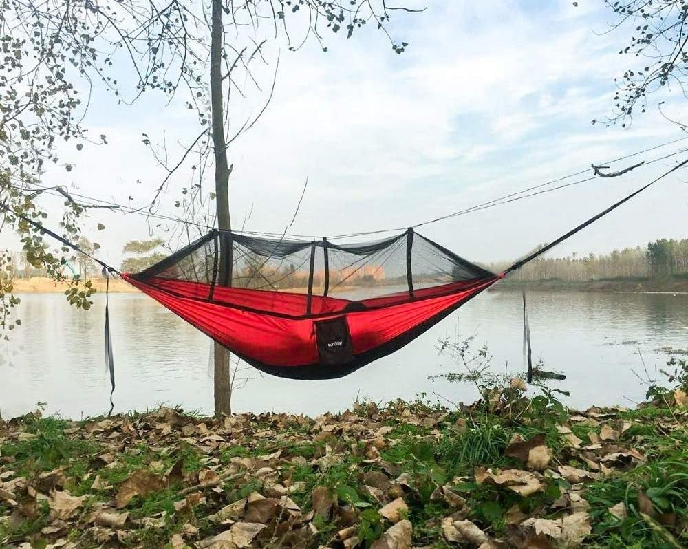red hammock strung up between two trees with a mosquito net on top
