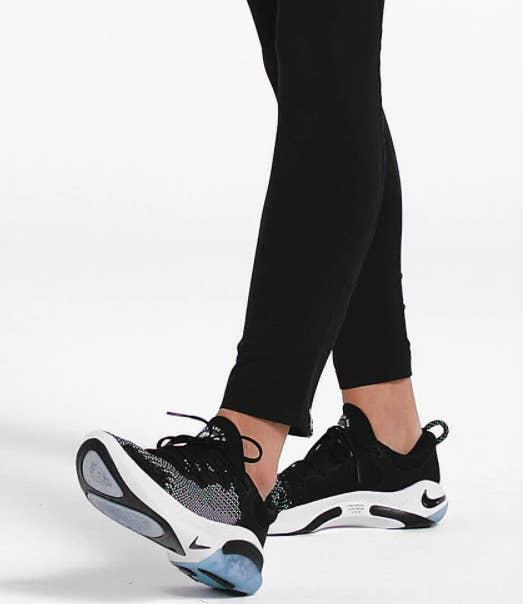 Model wears Nike Joyride Run Flyknit Shoes in a blue and green shade