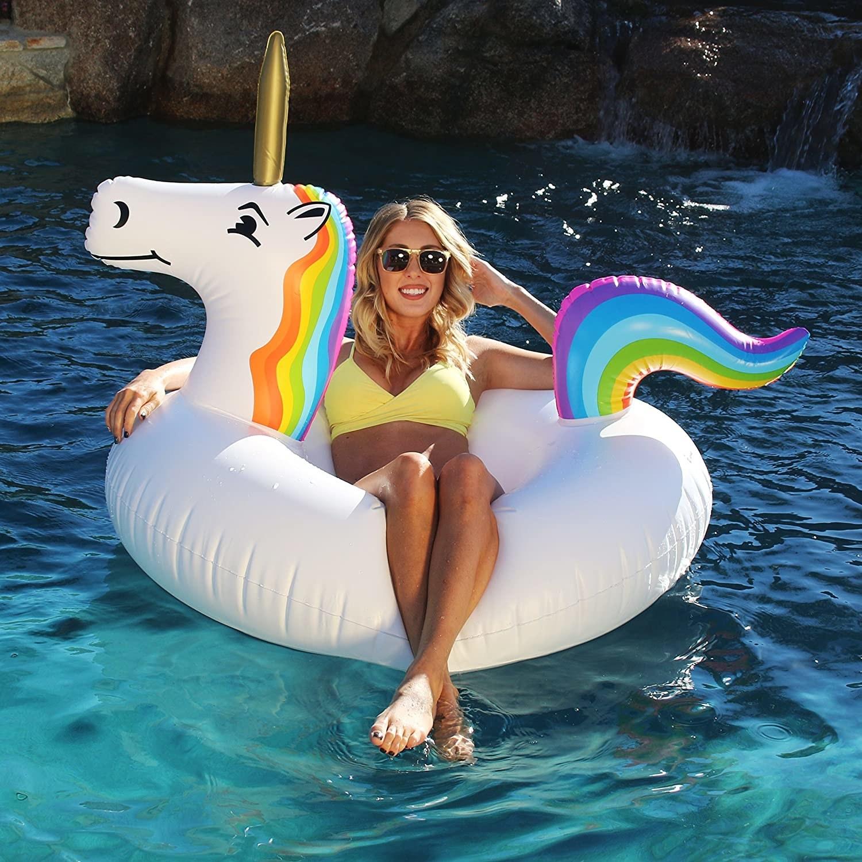 model sitting in unicorn pool float