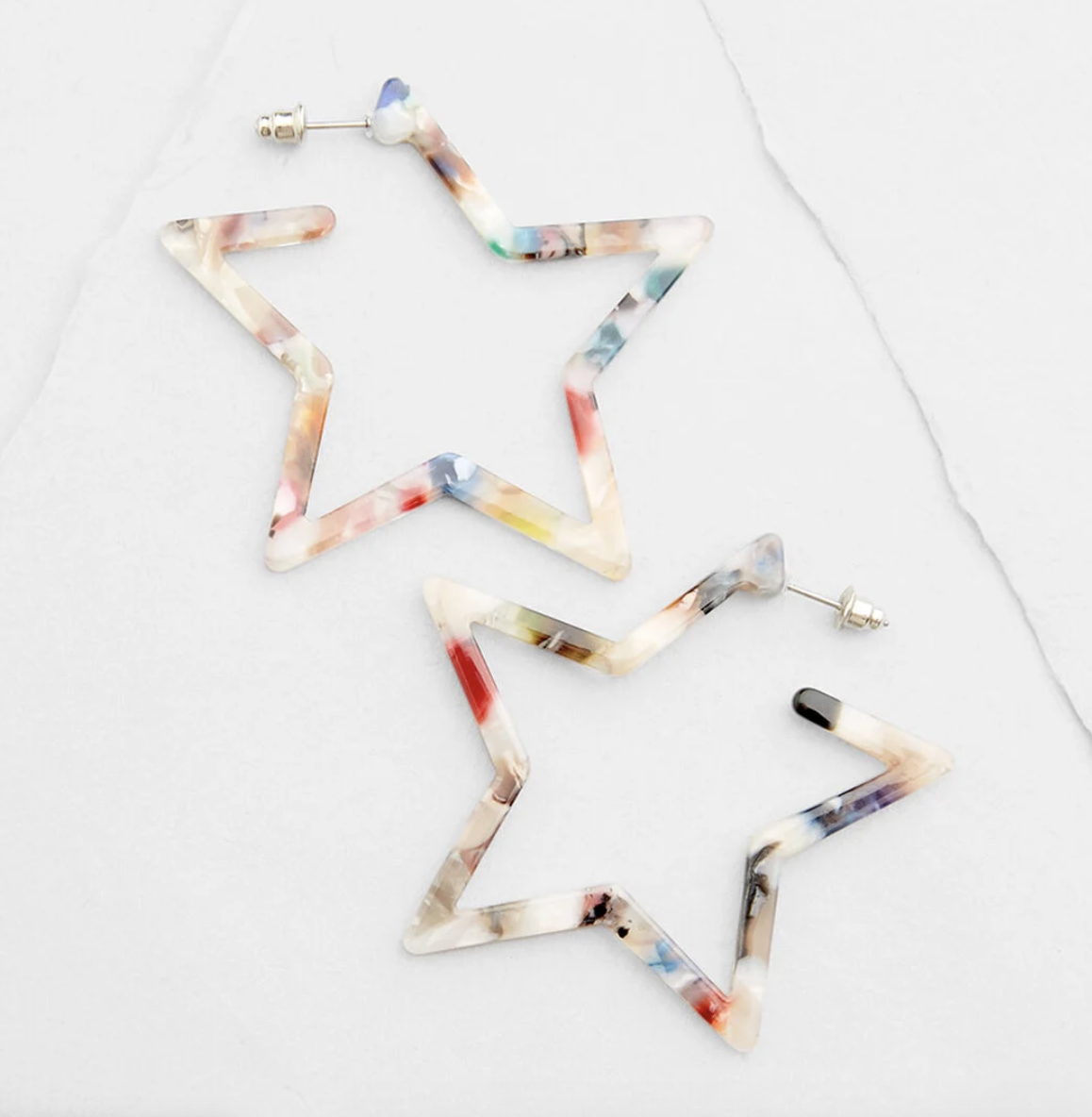 A pair of star-shaped marbled earrings with rainbow flecks