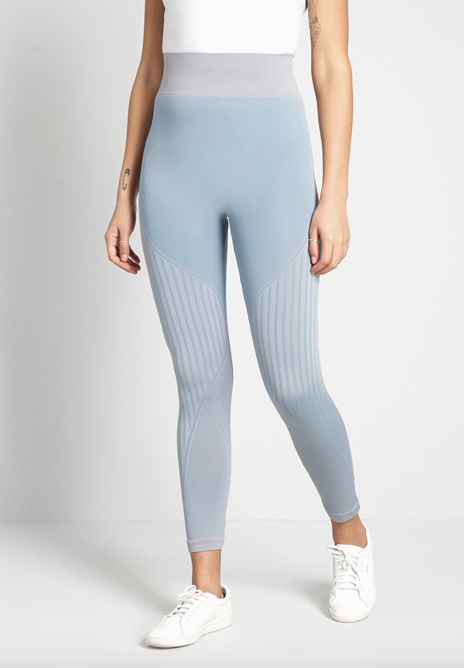 A model in the pale blue leggings, which have gray stripes and fall just above the ankle