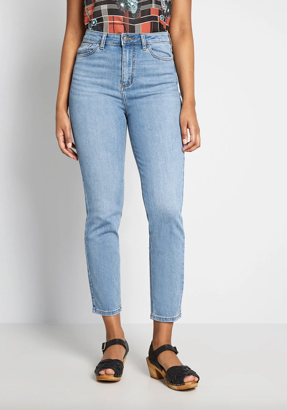 A model in lightwash high waist ankle jeans