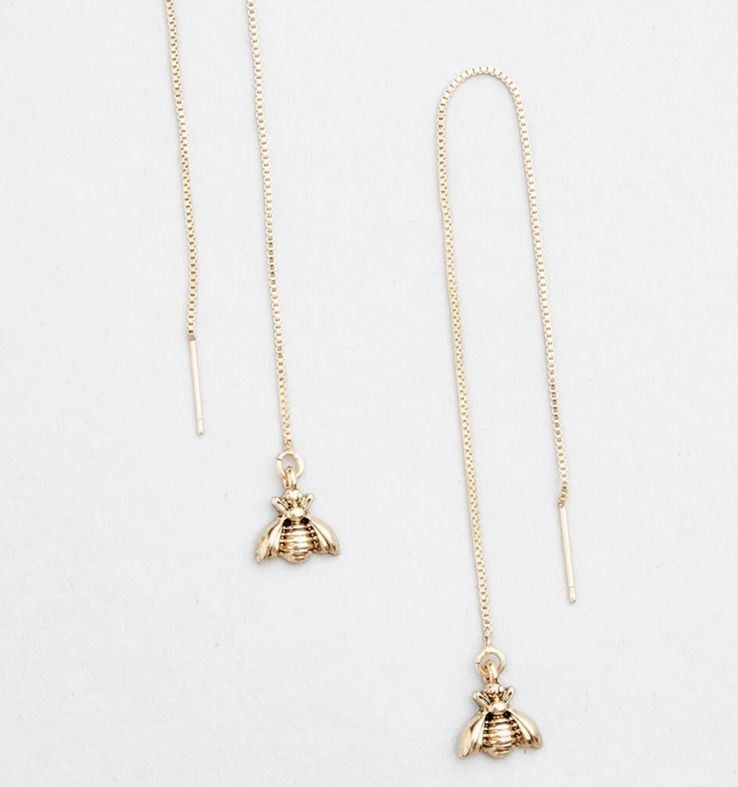 A pair fo gold threader earrings with little gold bees on the end