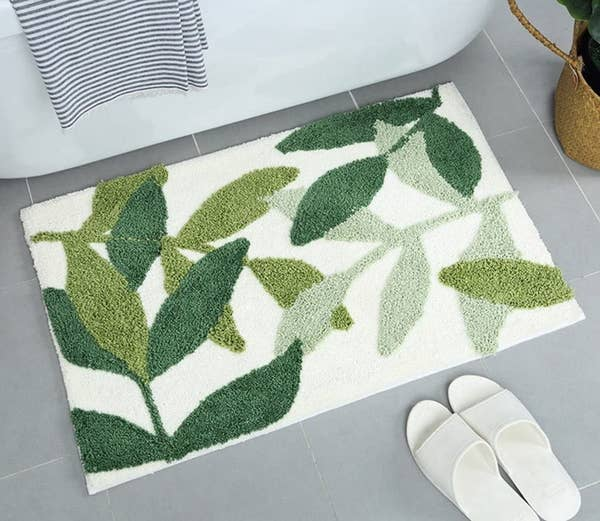 A white bath mat with leaves in three shades of green in front of a bathtub