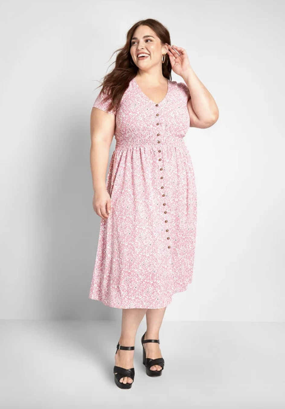 A model in a midi dress with short sleeves that buttons all the way up