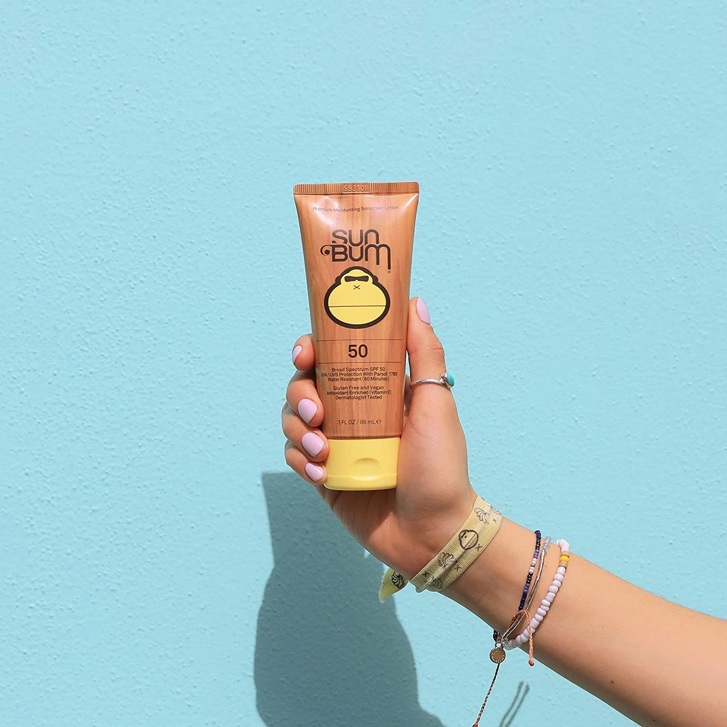 A model holding the tube of sunscreen