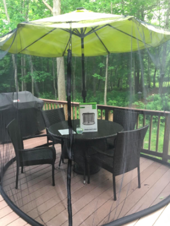 reviewer pic of the net on an umbrella on a deck with enough room for a table and four chairs inside