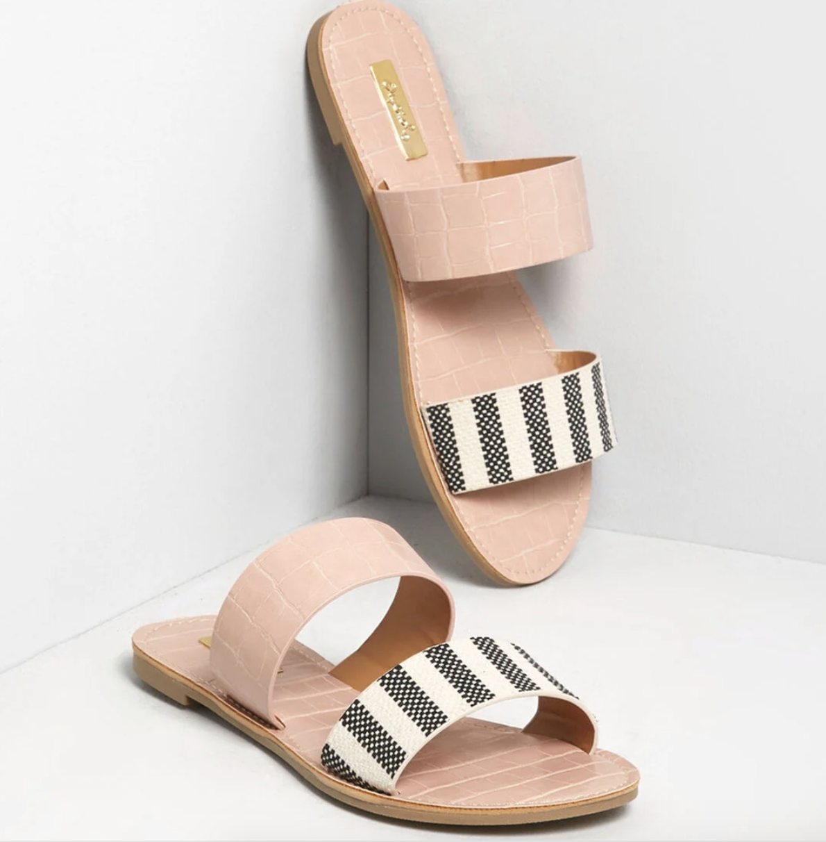 A pair of blush pink crocodile print slide-on sandals with two straps, one to match the rest of the shoe and the top one in black and white stripes