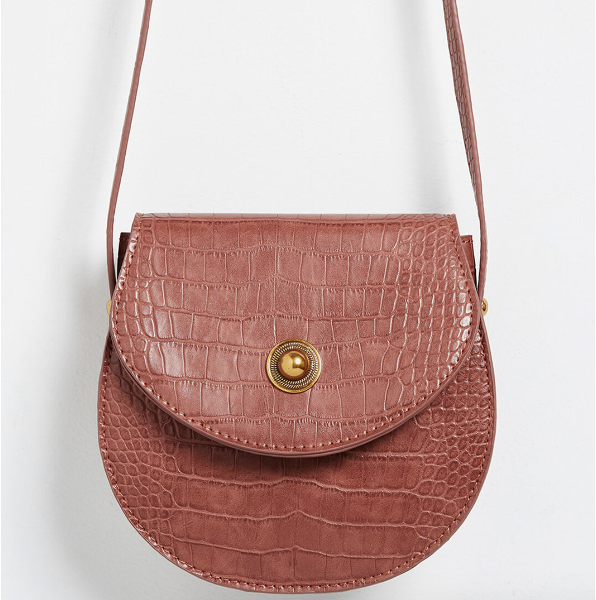 A demi-circle shaped crossbody bag with a magnetic closure on its flap