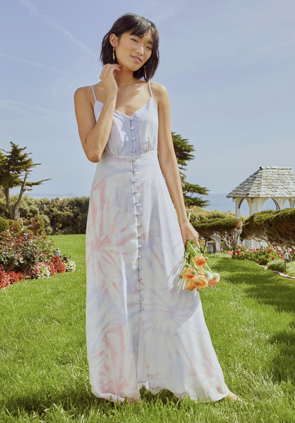 A model in a button up strapped tie-dye maxi dress
